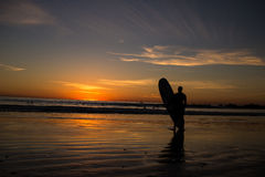 Серфер держа surfboard на заходе солнца пляжа Стоковые Фотографии RF