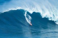 Серфер едет гигантская волна на челюстях Стоковая Фотография