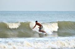 Серфер едет задняя сторона волны во время муссона на пляже Teluk Cempedak, Pahang, стоковые фотографии rf