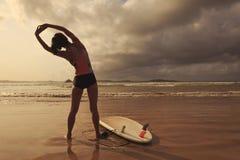 Серфер женщины нагревая на пляже Стоковая Фотография RF