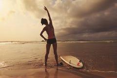 Серфер женщины нагревая на пляже Стоковые Изображения