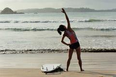 Серфер женщины нагревая на пляже Стоковые Фото