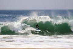 Серфер занимаясь серфингом большая волна на клине в пляже Калифорнии Ньюпорта стоковые фото