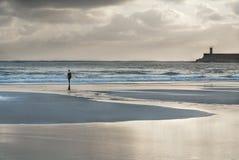 Серфер идя к морю на заходе солнца Стоковая Фотография