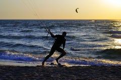 Серфер идя на берег на заходе солнца Стоковые Фотографии RF