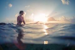 Серфер молодой дамы ждет волны стоковое изображение rf