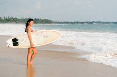 Серфер молодой дамы стоя на пляже с доской прибоя Стоковое фото RF
