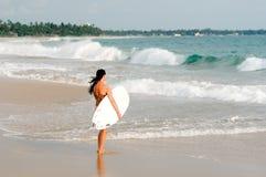 Серфер молодой дамы стоя на пляже с доской прибоя Стоковые Фото