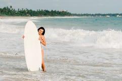 Серфер молодой дамы стоя на пляже с доской прибоя Стоковое Фото