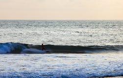 Серфер на голубой океанской волне в Бали Стоковая Фотография RF