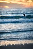 Серфер на заходе солнца пляжа на пляже и волнах вертикальных Стоковая Фотография RF