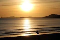 Серфер на пляже с заходом солнца позади Стоковое Изображение RF