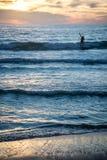 Серфер на пляже с заходом солнца в вертикальном формате Стоковая Фотография RF