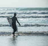 Серфер силуэта причаливает волнам, пляжу Fistral, Newquay, Корнуоллу стоковое изображение rf