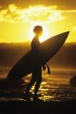 Серфер силуэта с Surfboard на заходе солнца Стоковая Фотография