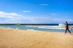 Серфер с доской идет вдоль моря стоковое фото rf