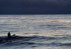 Серфер с surfboard в океане на залитой лунным светом ноче Стоковая Фотография RF
