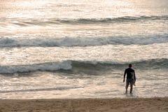 Серфер wading в воду рано утром стоковое изображение