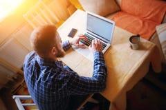 Серфинг сети в офисе Уверенно молодой человек работая на компьтер-книжке и усмехаясь пока сидящ на его месте службы в офисе Стоковые Изображения RF
