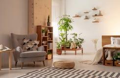 Серые кресло и pouf на ковре в современном интерьере открытого пространства с кроватью и заводами Реальное фото стоковая фотография