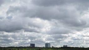 Серые ненастные облака бегут в небе над многоквартирными домами и древесинами сток-видео
