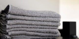 Серые полотенца полотенец на поле ванной комнаты Полотенца повешенные на крюках стоковая фотография rf