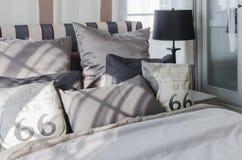 Серые подушки на кровати в современной спальне Стоковое фото RF