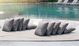 Серые подушки на расслабляющей кровати на бассейне на солнечный день Стоковое фото RF