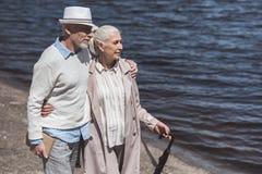 Серые с волосами пары идя на берег реки на дневном времени Стоковое фото RF