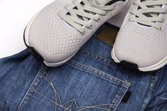 Серые тапки и джинсы Одежда для идти Одежда для перемещения Ботинки спорта и голубые джинсы Ботинки людей на белой предпосылке стоковые изображения rf