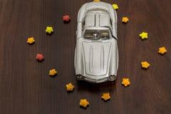 Серый автомобиль игрушки в красочном сахаре играет главные роли на деревянной предпосылке стоковое изображение