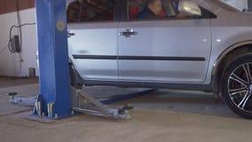 Серый автомобиль управляет в подъем автомобиля на станции обслуживания акции видеоматериалы