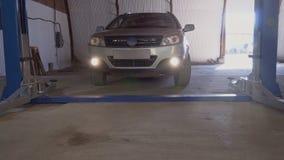 Серый автомобиль управляет в подъем автомобиля на станции обслуживания сток-видео