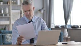 Серый бизнесмен волос работая на документах в офисе, обработке документов