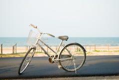 Серый велосипед припаркованный около пляжа Стоковые Изображения RF