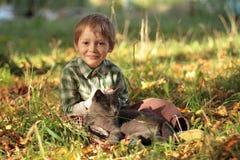 Серый кот и усмехаясь мальчик сидя на траве Малыш играя с котом Стоковое фото RF