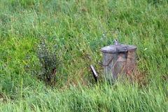 Серый металл тяжело - использовал мусорный бак рядом с высокорослыми цветками выведенными в середину высокой uncut травы стоковая фотография rf