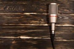 Серый микрофон на деревянной предпосылке Стоковые Изображения RF