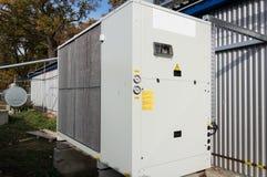 Серый промышленный холодильный агрегат стоя внешний на том основании близко к современному зданию производства стоковые фото