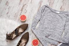 Серый свитер на деревянной предпосылке, коричневые ботинки, половина грейпфрута модная концепция Стоковое фото RF