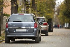 Серый сияющий автомобиль припаркованный в тихом районе на дороге асфальта на запачканной предпосылке bokeh на яркий солнечный ден стоковые изображения rf