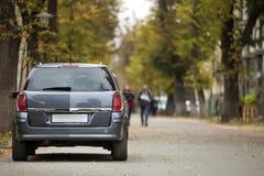 Серый сияющий автомобиль припаркованный в тихом районе на дороге асфальта на запачканной предпосылке bokeh на яркий солнечный ден стоковые фото
