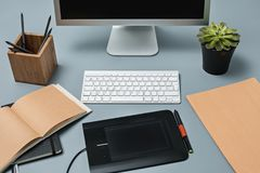 Серый стол с компьтер-книжкой, блокнотом с чистым листом, баком цветка, грифелем и таблеткой для ретушировать Стоковые Изображения RF