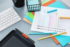 Серый стол с компьтер-книжкой, блокнотом с чистым листом, баком цветка, грифелем и таблеткой для ретушировать Стоковые Изображения