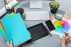 Серый стол с компьтер-книжкой, блокнотом с чистым листом, баком цветка, грифелем и таблеткой для ретушировать Стоковые Фото