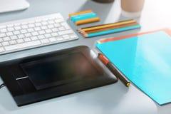 Серый стол с компьтер-книжкой, блокнотом с чистым листом, баком цветка, грифелем и таблеткой для ретушировать Стоковое фото RF