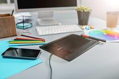 Серый стол с компьтер-книжкой, блокнотом с чистым листом, баком цветка, грифелем и таблеткой для ретушировать Стоковые Фотографии RF