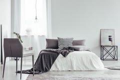 Серый стул в белой спальне стоковые изображения