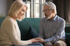 Серый с волосами супруг утешая жену, держащ руки, показывая поддержку стоковое фото rf
