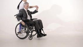 Серый с волосами человек в кресло-коляске танцует с азиатской смотря медсестрой акции видеоматериалы